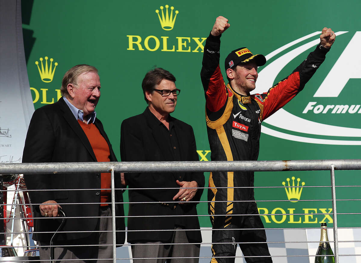 """COTA co-owner B.J. """"Red"""" McCombs (from left) and Texas Governor Rick Perry watch Lotus F1 driver and USGP second place winner Romain Grosjean react to the crowd after the Formula One United States Grand Prix at the Circuit of the Americas near Austin, Texas on Sunday, Nov. 17, 2013. Current World Champion Sebastian Vettle finished first followed by Grojean and in third was Vettel's teammate, Mark Webber."""