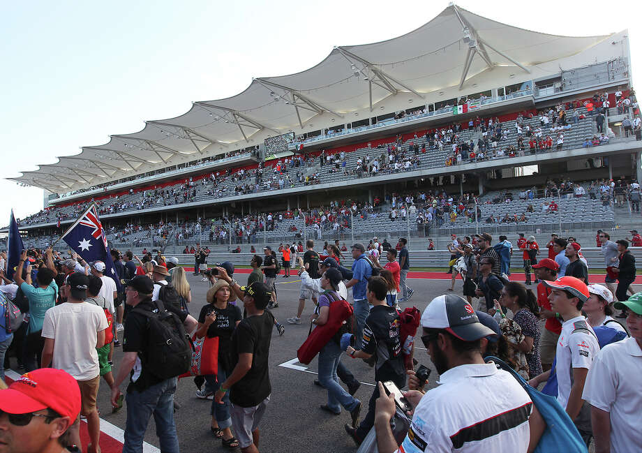 Fans flock to the track after the Formula One United States Grand Prix at the Circuit of the Americas near Austin, Texas on Sunday, Nov. 17,  2013. Current World Champion Sebastian Vettle finished first in the race followed by Lotus F1's Romain Grosjean and in third was Vettel's teammate, Mark Webber. Photo: Kin Man Hui, San Antonio Express-News / ©2013 San Antonio Express-News