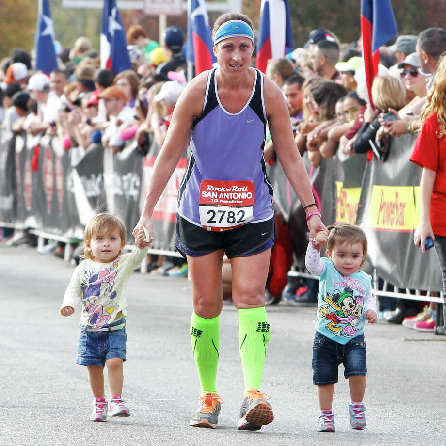 Nicle Notarianni of Austin and her 1-1/2-year old daughters Liliana (left) and Jilian approach the finish line of the half marathon during the Rock 'n' Roll San Antonio Marathon and 1/2 Marathon on Sunday, Nov. 17, 2013. Photo: Marvin Pfeiffer, San Antonio Express-News / Express-News 2013