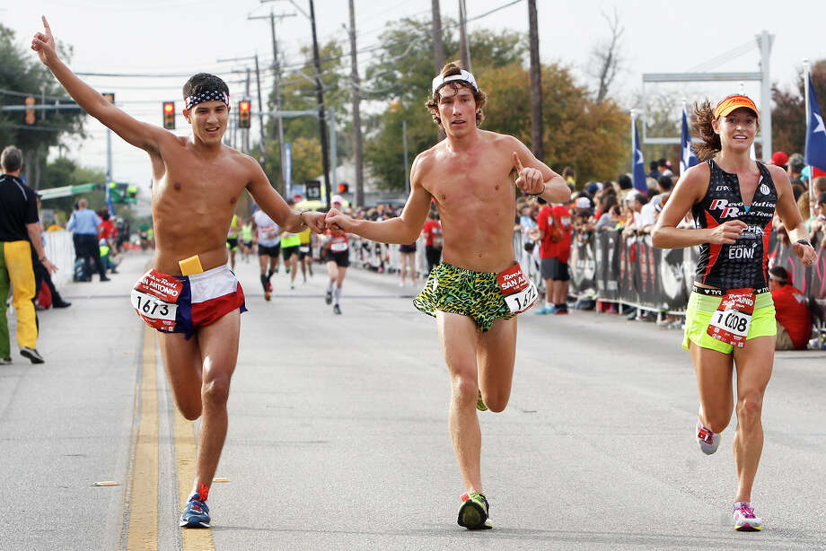 Two runners bump fists as they approach the finish line of the half marathon during the Rock 'n' Roll San Antonio Marathon and 1/2 Marathon on Sunday, Nov. 17, 2013. Photo: Marvin Pfeiffer, San Antonio Express-News / Express-News 2013
