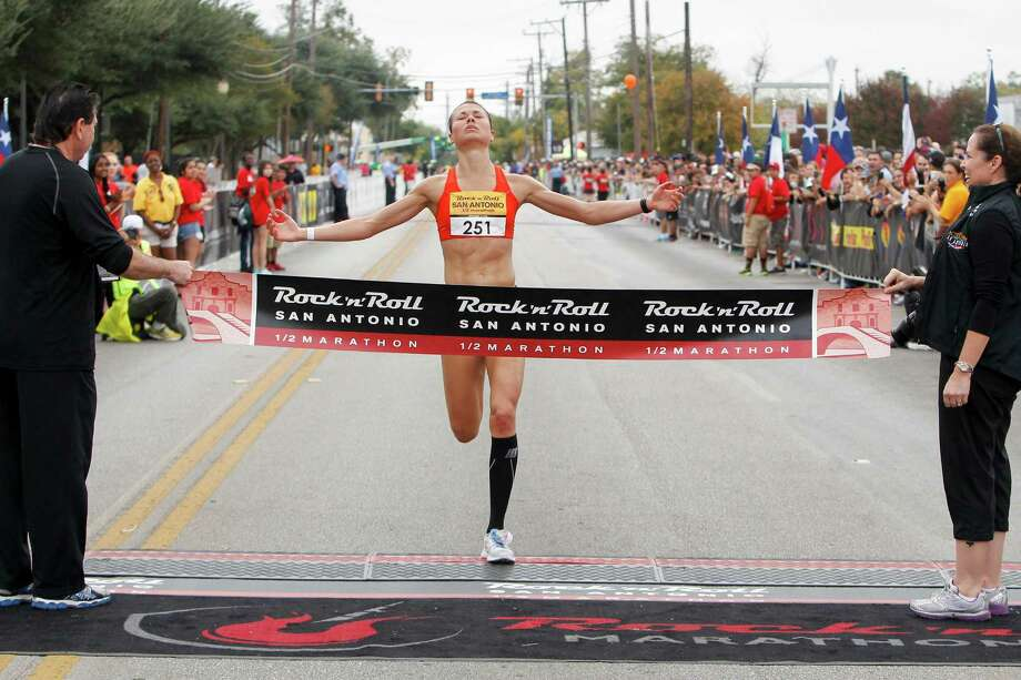 Dani Fisher of Wausau, Wis., approaches the finish line of the half marathon during the Rock 'n' Roll San Antonio Marathon and 1/2 Marathon on Sunday, Nov. 17, 2013.  Fisher took the women's title in the 1/2 marathon with a time of 1:18.58. Photo: Marvin Pfeiffer, San Antonio Express-News / Express-News 2013