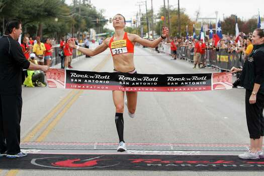 Dani Fisher of Wausau, Wis., crosses the finish line of the half marathon during the Rock 'n' Roll San Antonio Marathon and 1/2 Marathon on Sunday, Nov. 17, 2013.  Fisher took the women's title in the 1/2 marathon with a time of 1:18.58. Photo: Marvin Pfeiffer, San Antonio Express-News / Express-News 2013