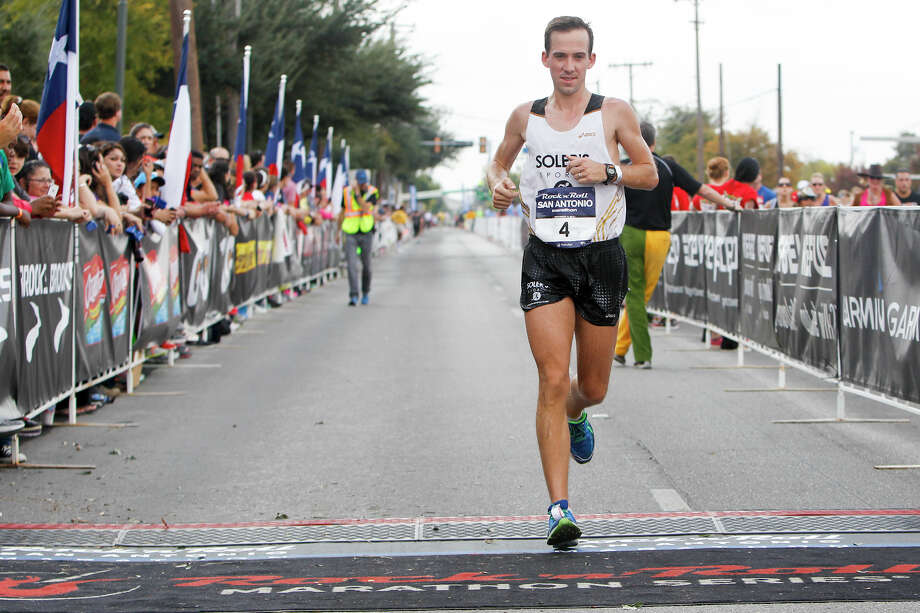 Jeremy Daum of San Antonio crosses the finish line of the marathon during the Rock 'n' Roll San Antonio Marathon and 1/2 Marathon on Sunday, Nov. 17, 2013.  Daum was the third men's finisher in the marathon with a time of 2:39.37. Photo: Marvin Pfeiffer, San Antonio Express-News / Express-News 2013