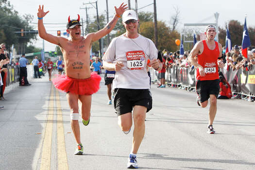 A runner with Devil horns and a tutu (left) approaches the finish line of the half marathon with others during the Rock 'n' Roll San Antonio Marathon and 1/2 Marathon on Sunday, Nov. 17, 2013. Photo: Marvin Pfeiffer, San Antonio Express-News / Express-News 2013