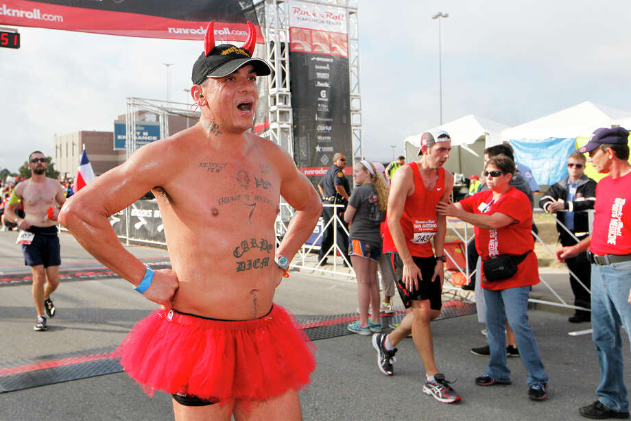 A runner with Devil horns and a tutu after crossing the finish line of the half marathon with others during the Rock 'n' Roll San Antonio Marathon and 1/2 Marathon on Sunday, Nov. 17, 2013. Photo: Marvin Pfeiffer, San Antonio Express-News / Express-News 2013