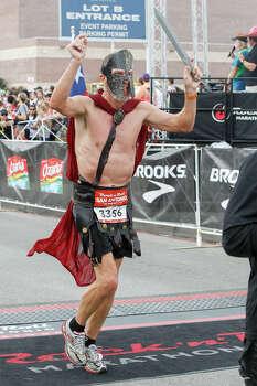 Paul Baltutis of San Antonio crosses the finish line of the half marathon in gladiator garb during the Rock 'n' Roll San Antonio Marathon and 1/2 Marathon on Sunday, Nov. 17, 2013. Photo: Marvin Pfeiffer, San Antonio Express-News / Express-News 2013