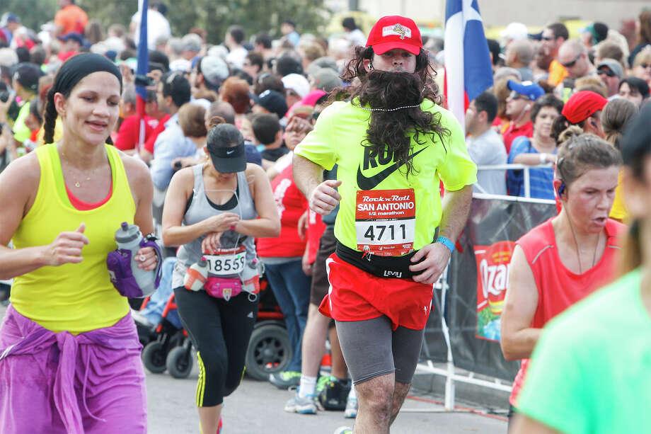 Michael Haws of San Antonio approaches the finish line of the half marathon sporting a fake beard during the Rock 'n' Roll San Antonio Marathon and 1/2 Marathon on Sunday, Nov. 17, 2013. Photo: Marvin Pfeiffer, San Antonio Express-News / Express-News 2013