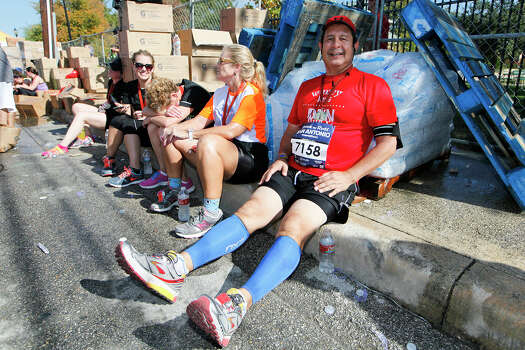 Joe Cortinas of Del Rio rests his legs as he sits with his back on a pile of ice after finishing the Rock 'n' Roll San Antonio Marathon and 1/2 Marathon on Sunday, Nov. 17, 2013. Photo: Marvin Pfeiffer, San Antonio Express-News / Express-News 2013