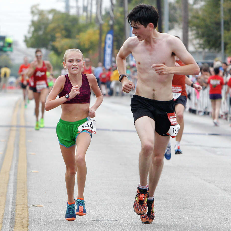 Louie Tijerina of Brownsville (right) urges on thirteen-year-old Katlyn Welsch of Alvin as they approach the finish line of the half marathon during the Rock 'n' Roll San Antonio Marathon and 1/2 Marathon on Sunday, Nov. 17, 2013. Photo: Marvin Pfeiffer, San Antonio Express-News / Express-News 2013