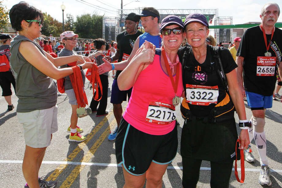 Kimberly Ursery of Sugar Land (center) and Paula Mitchell of Boerne celebrate after receiving their medals following the Rock 'n' Roll San Antonio Marathon and 1/2 Marathon on Sunday, Nov. 17, 2013. Photo: Marvin Pfeiffer, San Antonio Express-News / Express-News 2013
