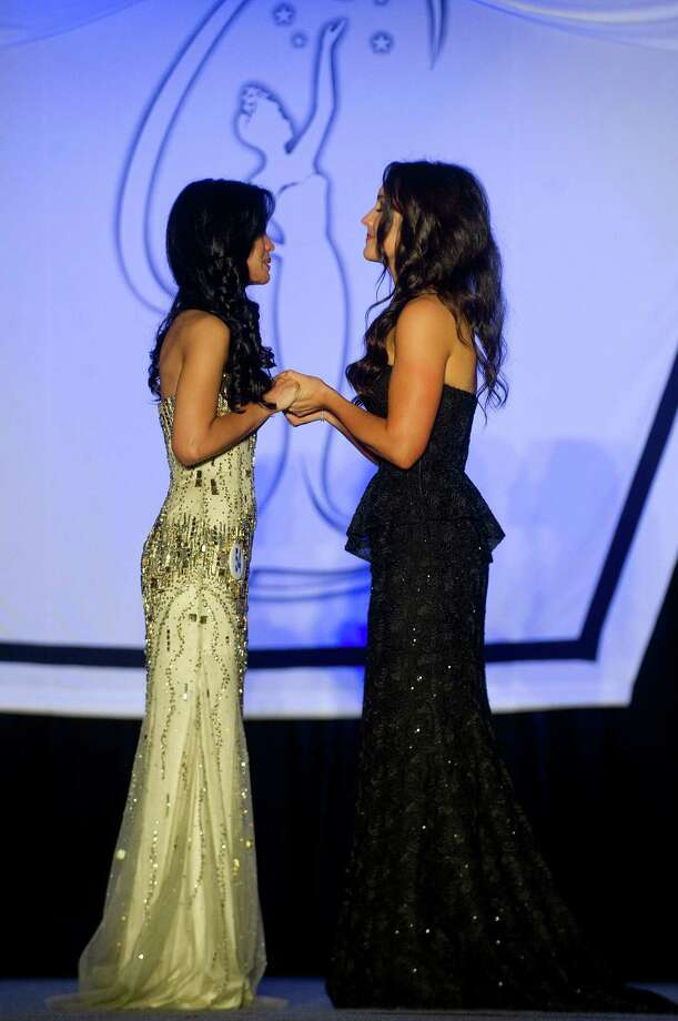 Desirée Pérez of Greenwich and Nikki Delventhal of Fairfield hold hands as they wait to hear who won the Miss Connecticut USA pageant at the Stamford Marriott in Stamford, Conn., on Sunday, November 17, 2013. Pérez won the competition and will compete for Miss USA. Photo: Lindsay Perry / Stamford Advocate