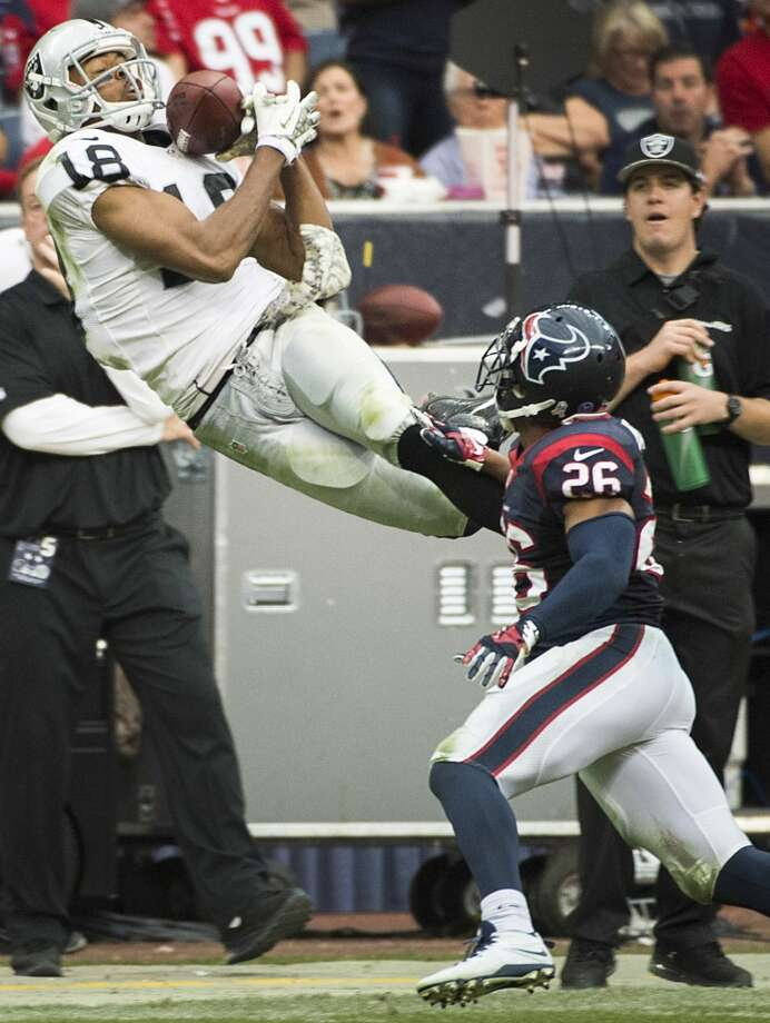 Raiders wide receiver Andre Holmes (18) leaps for a pass as Texans defensive back Brandon Harris (26) defends. Photo: Smiley N. Pool, Houston Chronicle