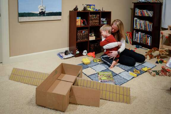 NASA astronaut Karen Nyberg plays with her son Jack at their home in League City on Wednesday, Nov. 13, 2013, in Houston.  Having  returned from space on Nov. 11, after 166 days aboard the International Space Station, her son asked her to help him build a space station out of cardboard as soon as she was home. Nyberg and her husband, fellow astronaut Doug Hurley, have shared their parenting duties through training and two space missions.  Her long duration stay aboard the ISS and his mission as the pilot of the final space shuttle flight in 2011.