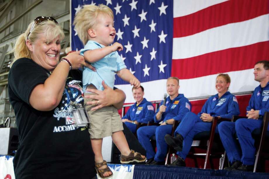 The crew of STS-135, from left, commander Chris Ferguson, pilot Doug Hurley, and mission specialists Sandy Magnus and Rex Walheim watch as a Hurley's son Jack is scooped up as he tried to run up to the stage during a welcome home ceremony for the crew of the space shuttle Atlantis, the final mission of the NASA shuttle program, at Ellington Field in Houston on Friday, July 22, 2011. Photo: Smiley N. Pool, Houston Chronicle / © 2011  Houston Chronicle