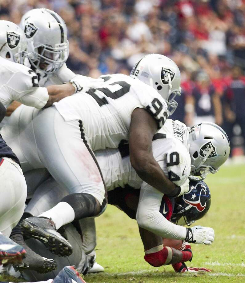 Raiders defensive tackle Stacy McGee (92) and linebacker Kevin Burnett (94) stop Texans running back Ben Tate (44) for a loss on the goal line. Photo: Brett Coomer, Houston Chronicle