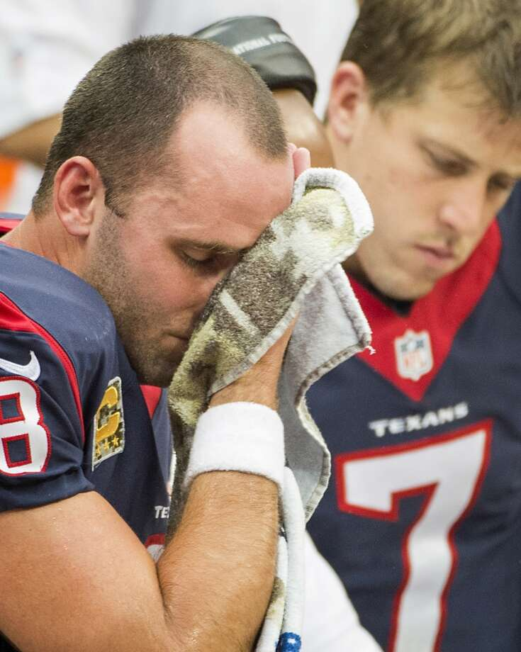 Texans quarterback Matt Schaub wipes his face on the bench as he sits with Case Keenum. Photo: Smiley N. Pool, Houston Chronicle
