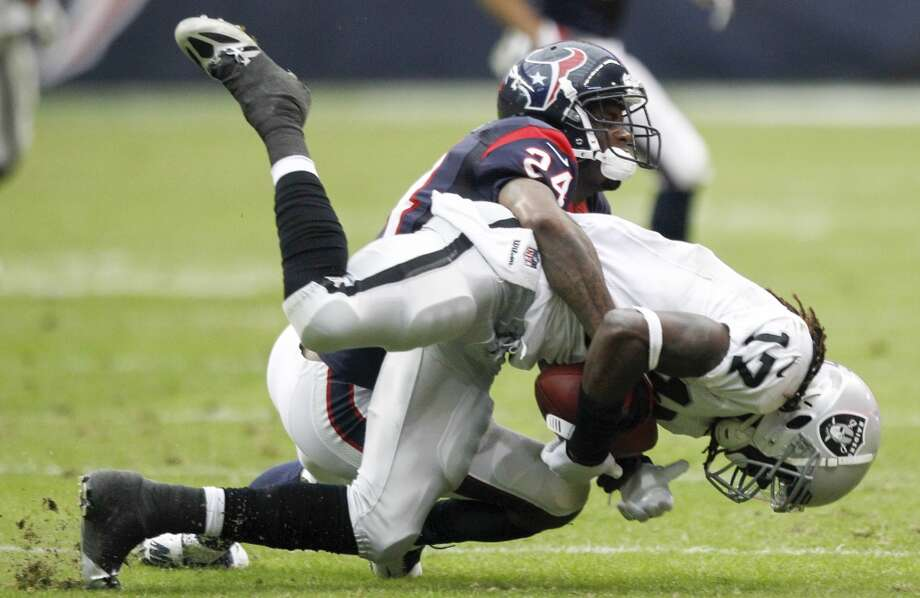 Texans cornerback Johnathan Joseph tackles Raiders wide receiver Denarius Moore. Photo: Brett Coomer, Houston Chronicle