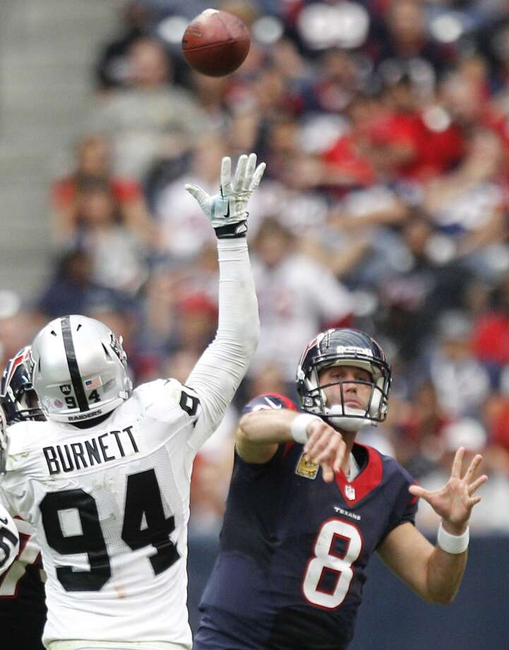 Texans quarterback Matt Schaub throws a pass over Raiders linebacker Kevin Burnett. Photo: Brett Coomer, Houston Chronicle