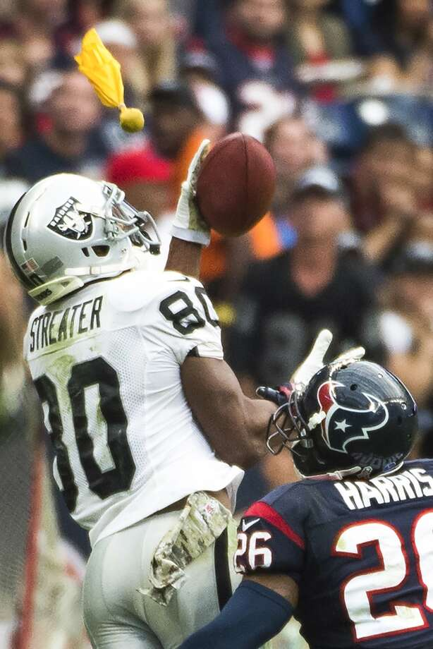 Raiders wide receiver Rod Streater (80) reaches for a catch as Texans defensive back Brandon Harris (26) flagged for a penalty. Photo: Smiley N. Pool, Houston Chronicle