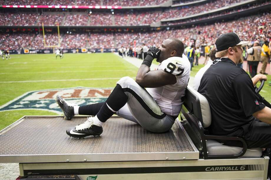 Raiders defensive tackle Daniel Muir  leaves the game on a cart. Photo: Smiley N. Pool, Houston Chronicle