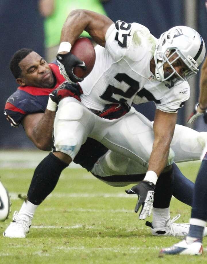 Texans inside linebacker Darryl Sharpton loses his helmet as he hits Raiders running back Rashad Jennings. Photo: Brett Coomer, Houston Chronicle