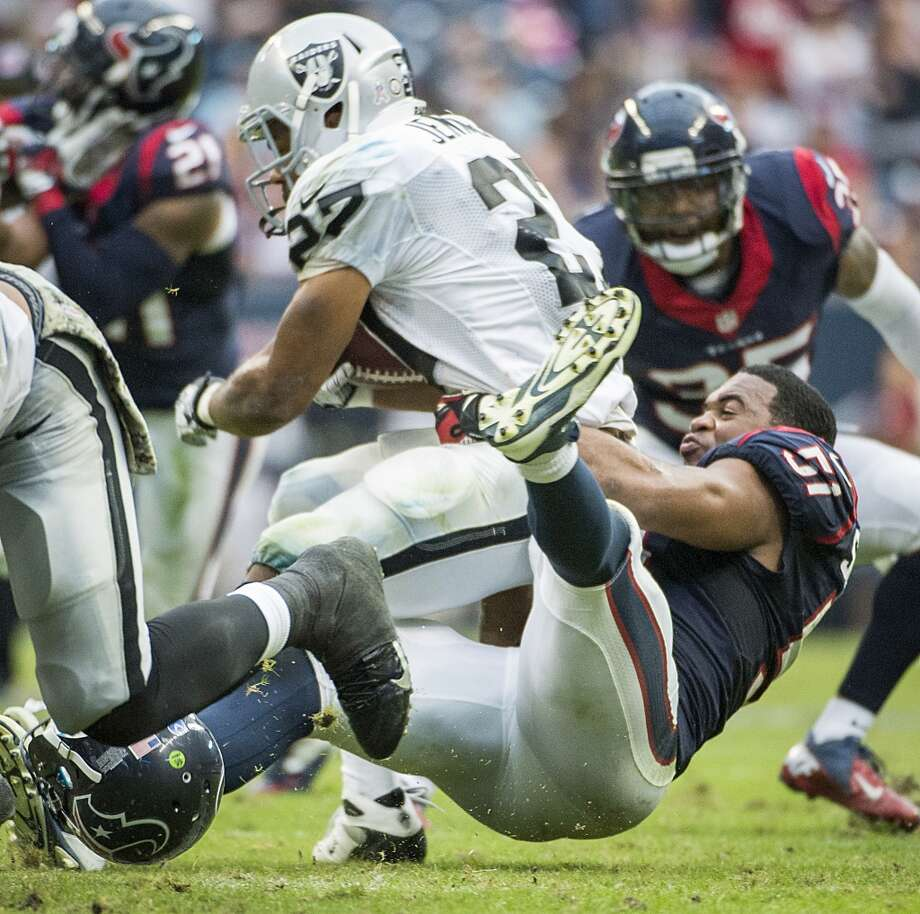 Texans inside linebacker Darryl Sharpton brings down Raiders running back Rashad Jennings. Photo: Smiley N. Pool, Houston Chronicle
