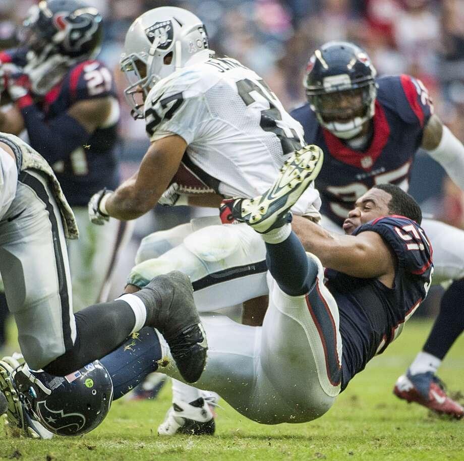 Texans inside linebacker Darryl Sharpton brings down Raiders running back Rashad Jennings. Photo: Smiley N. Pool, Houston Chronicle