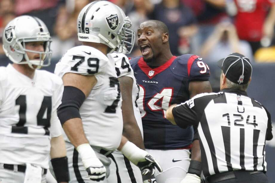Texans defensive end Antonio Smith (94) yells at Raiders center Andre Gurode (64) as umpire Carl Paganelli (124) runs in to break them up. Photo: Brett Coomer, Houston Chronicle