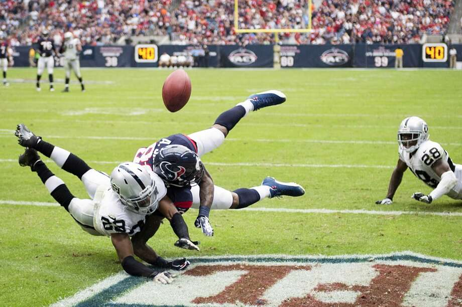 Texans wide receiver Andre Johnson and Raiders strong safety Brandian Ross dive for a pass in the end zone. Photo: Smiley N. Pool, Houston Chronicle