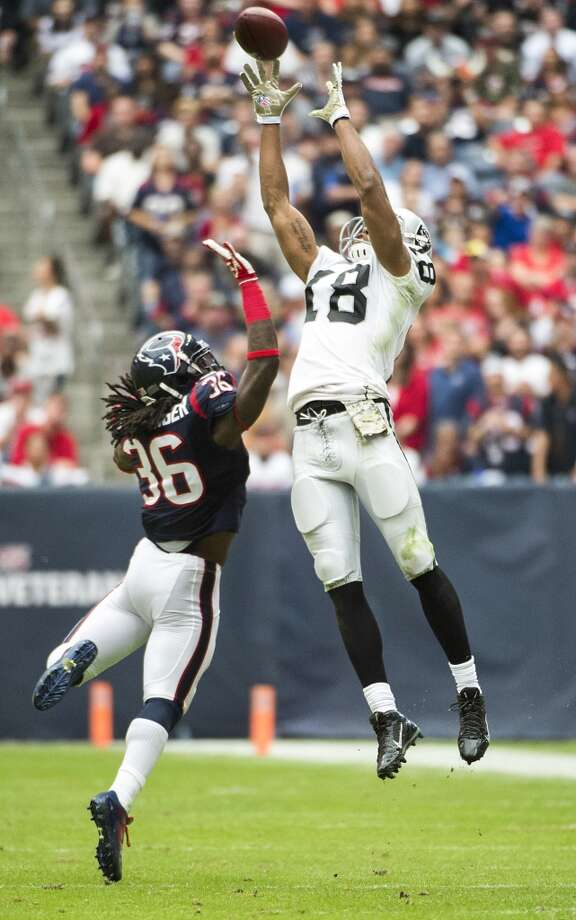 Raiders wide receiver Andre Holmes (18) makes a catch over Texans strong safety D.J. Swearinger. Photo: Smiley N. Pool, Houston Chronicle