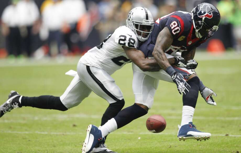 Raiders cornerback Phillip Adams (28) breaks up a pass intended for Texans wide receiver Andre Johnson. Photo: Brett Coomer, Houston Chronicle
