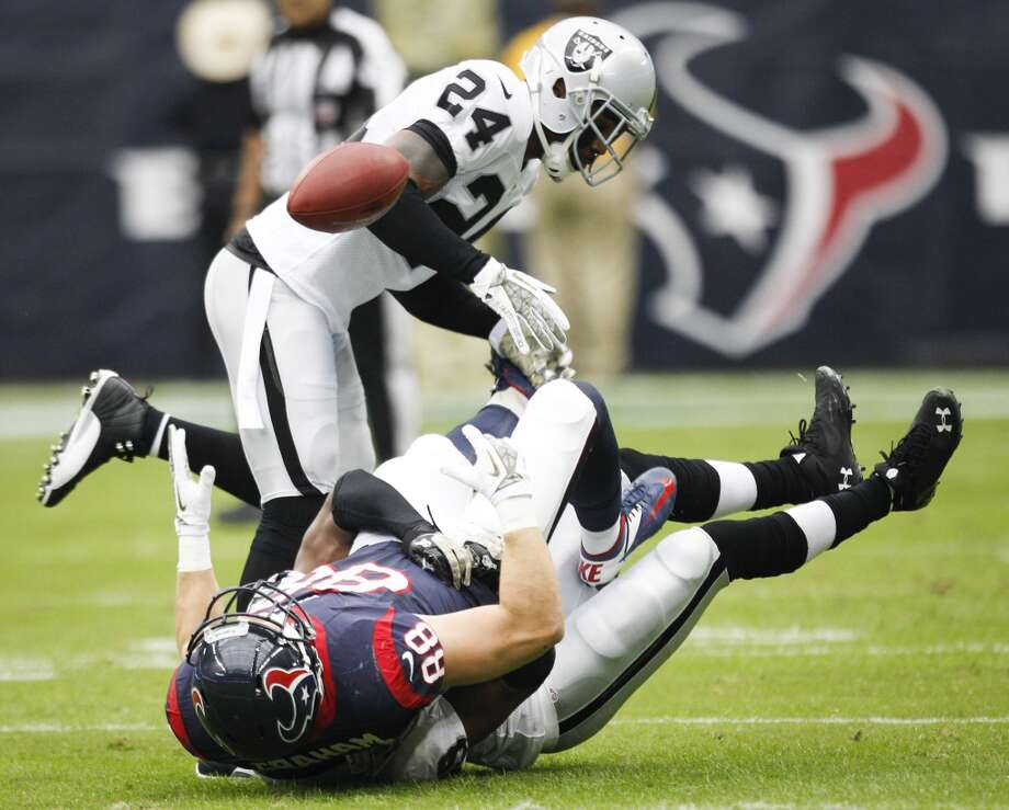 Texans tight end Garrett Graham (88) fumbles as he is hit by Raiders strong safety Brandian Ross (29) and free safety Charles Woodson (24) on the opening drive. Photo: Brett Coomer, Houston Chronicle