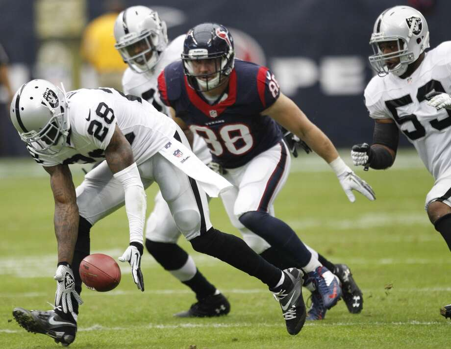Raiders cornerback Phillip Adams (28) picks up a fumble by Texans tight end Garrett Graham (88). Photo: Brett Coomer, Houston Chronicle