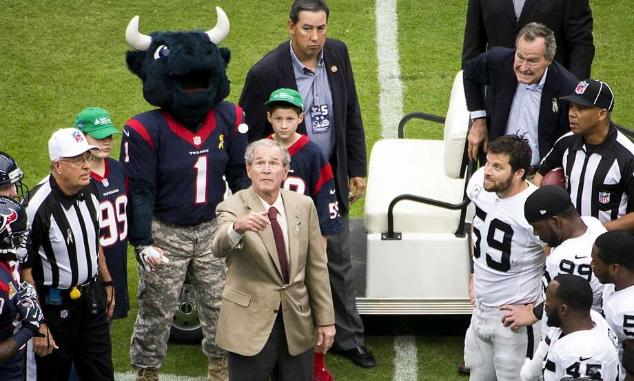 Former President George W. Bush performs the opening coin toss as President George H. W. Bush looks on before the Texans face the Raiders. Photo: Smiley N. Pool, Houston Chronicle