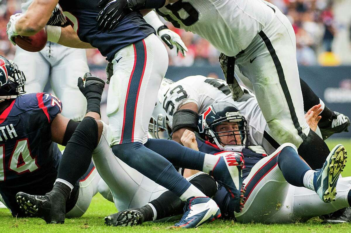 After being laid out by a Nick Roach hit, Texans quarterback Case Keenum, right, sees Garrett Graham scoop up his fumble.