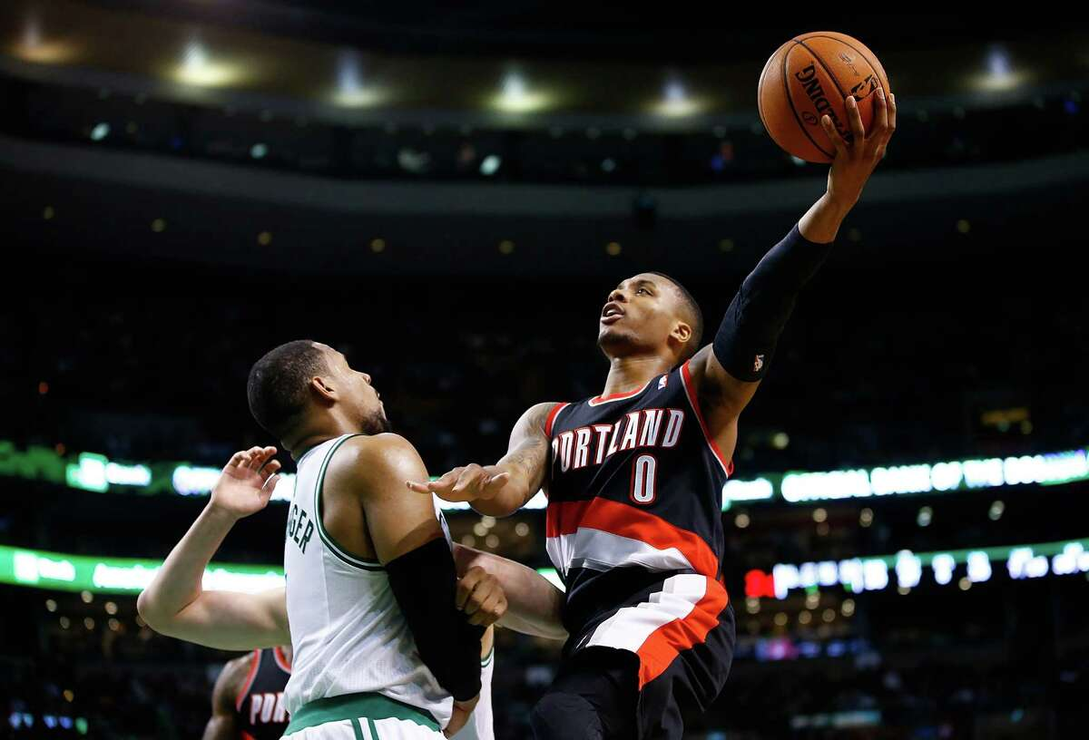 BOSTON, MA - NOVEMBER 15: Damian Lillard #0 of the Portland Trailblazers drives to the basket in front of Jared Sullinger #7 of the Boston Celtics in the second half during the game at TD Garden on November 15, 2013 in Boston, Massachusetts. (Photo by Jared Wickerham/Getty Images) ORG XMIT: 182407598