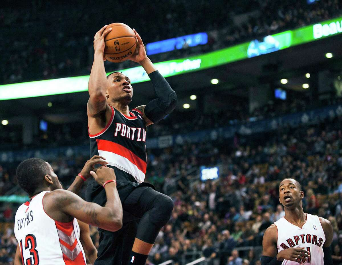 Portland Trail Blazers Damian Lillard goes to the net against the Toronto Raptors during an NBA basketball game in Toronto on Sunday, Nov. 17, 2013. (AP Photo/The Canadian Press, Aaron Vincent Elkaim) ORG XMIT: AVE114