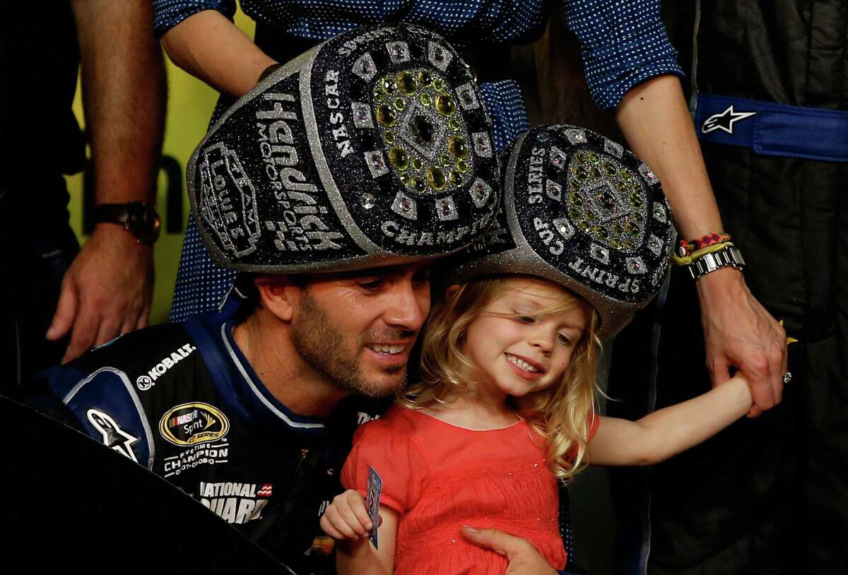 HOMESTEAD, FL - NOVEMBER 17: Jimmie Johnson, driver of the #48 Lowe's/Kobalt Tools Chevrolet, celebrates in Champions Victory Lane with his daughter Genevieve Marie after winning the series championship following the NASCAR Sprint Cup Series Ford EcoBoost 400 at Homestead-Miami Speedway on November 17, 2013 in Homestead, Florida. (Photo by Chris Graythen/Getty Images) ORG XMIT: 159337956