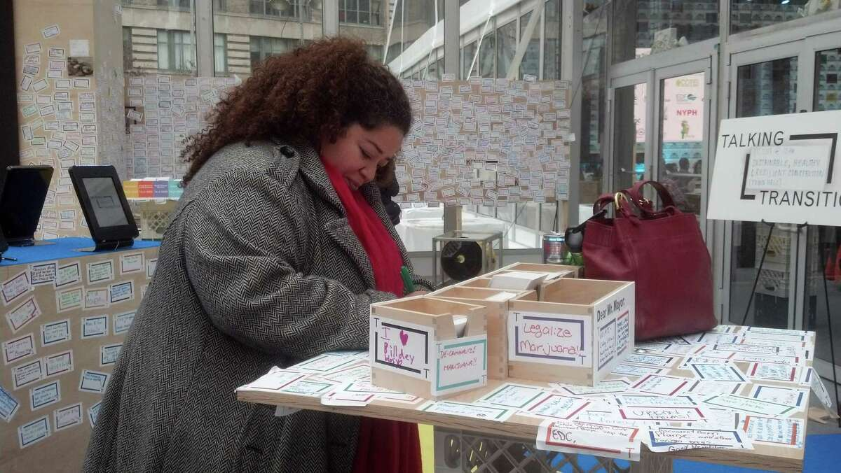 """Taireina Gilbert writes a suggestion for Mayor-Elect Bill de Blasio, in a """"transition tent"""" in New York's Lower Manhattan where New Yorkers can come share their concerns about the city, Sunday, Nov. 17, 2013. Gilbert, belongs to a group called Farm School NYC, an organization that plants produce cheaper than what's in city supermarkets. Her note read: """"Support for small community owned business!"""" (AP Photo/Verena Dobnik) ORG XMIT: NYR101"""