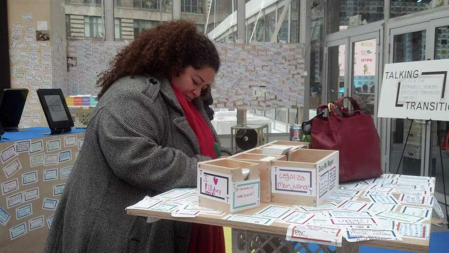 """Taireina Gilbert writes a suggestion for Mayor-Elect Bill de Blasio, in a """"transition tent"""" in New York's Lower Manhattan where New Yorkers can come share their concerns about the city, Sunday, Nov. 17, 2013. Gilbert, belongs to a group called Farm School NYC, an organization that plants produce cheaper than what's in city supermarkets. Her note read: """"Support for small community owned business!"""" (AP Photo/Verena Dobnik) ORG XMIT: NYR101 Photo: Verena Dobnik / AP"""