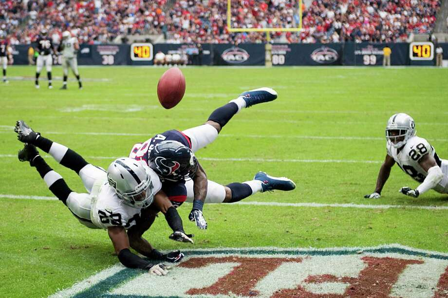 Texans receiver Andre Johnson (80) and Raiders strong safety Brandian Ross (29) collide in the end zone on a first-half incompletion Sunday. Johnson finished with 10 catches for 116 yards, his 19th career 10-100 game. Photo: Smiley N. Pool, Staff / © 2013  Houston Chronicle