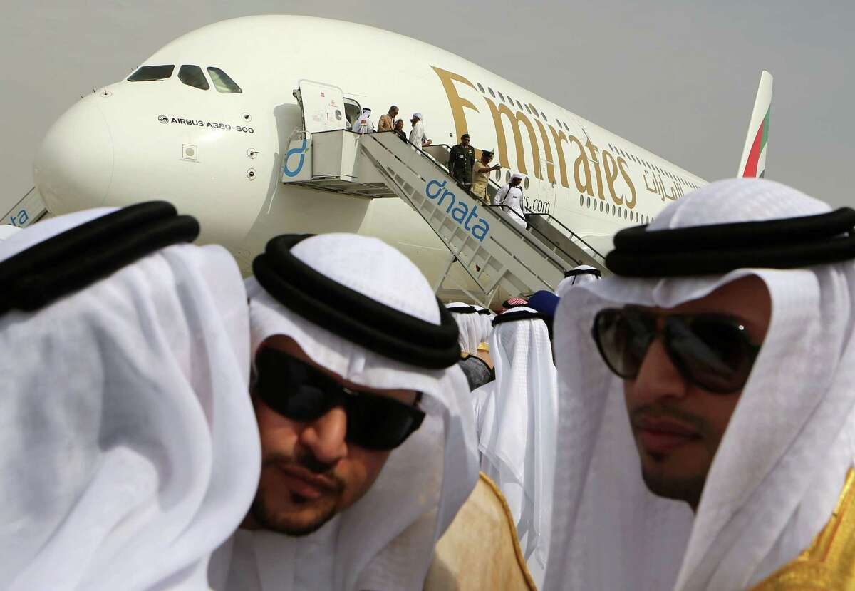 Emirati officials greet each other in front of an Emirates Airbus A380 on display during the opening day of the Dubai Airshow in Dubai, United Arab Emirates, Sunday Nov. 17, 2013. The Dubai Airshow is seen as an increasingly important barometer on the state of the industry and the rising roles of the big-spending Gulf carriers Etihad, Qatar Airways and Emirates as they compete for routes and critical stopover traffic between Asia and Europe and the Americas. (AP Photo/Kamran Jebreili) ORG XMIT: XKJ108