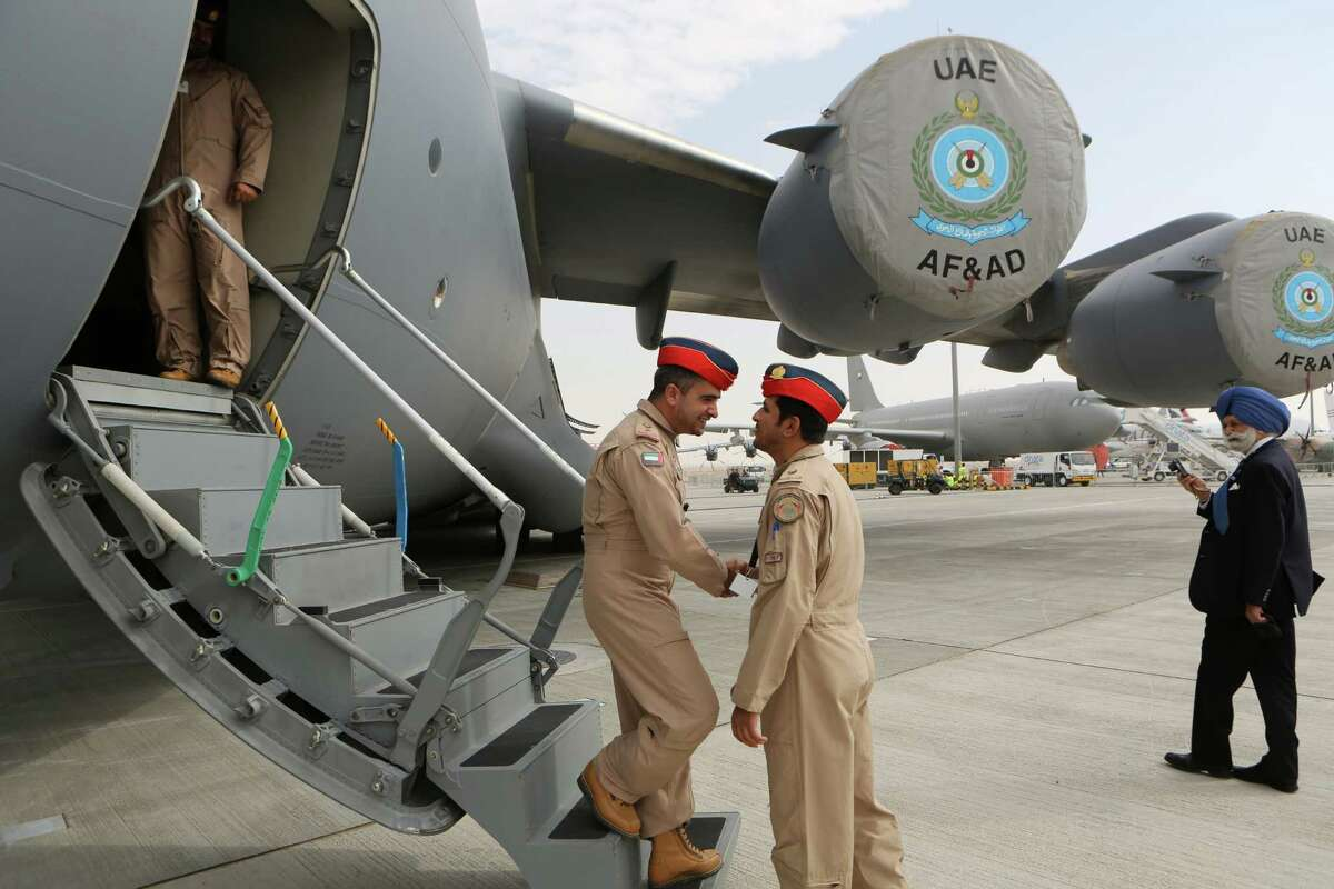 UAE pilots greet each other at the steps of a Boeing C-17 Globemaster III, a large military transport aircraft of the UAE Air forces during the opening day of the Dubai Airshow in Dubai, United Arab Emirates, Sunday Nov. 17, 2013. Boeing Co.'s planned 777X long-haul airliner grabbed the bulk of orders Sunday at the first day of the Dubai Airshow, with at least 225 planes on the books in an eye-popping display of the spending power and aggressive expansion efforts of Gulf carriers. (AP Photo/Kamran Jebreili) ORG XMIT: XKJ106