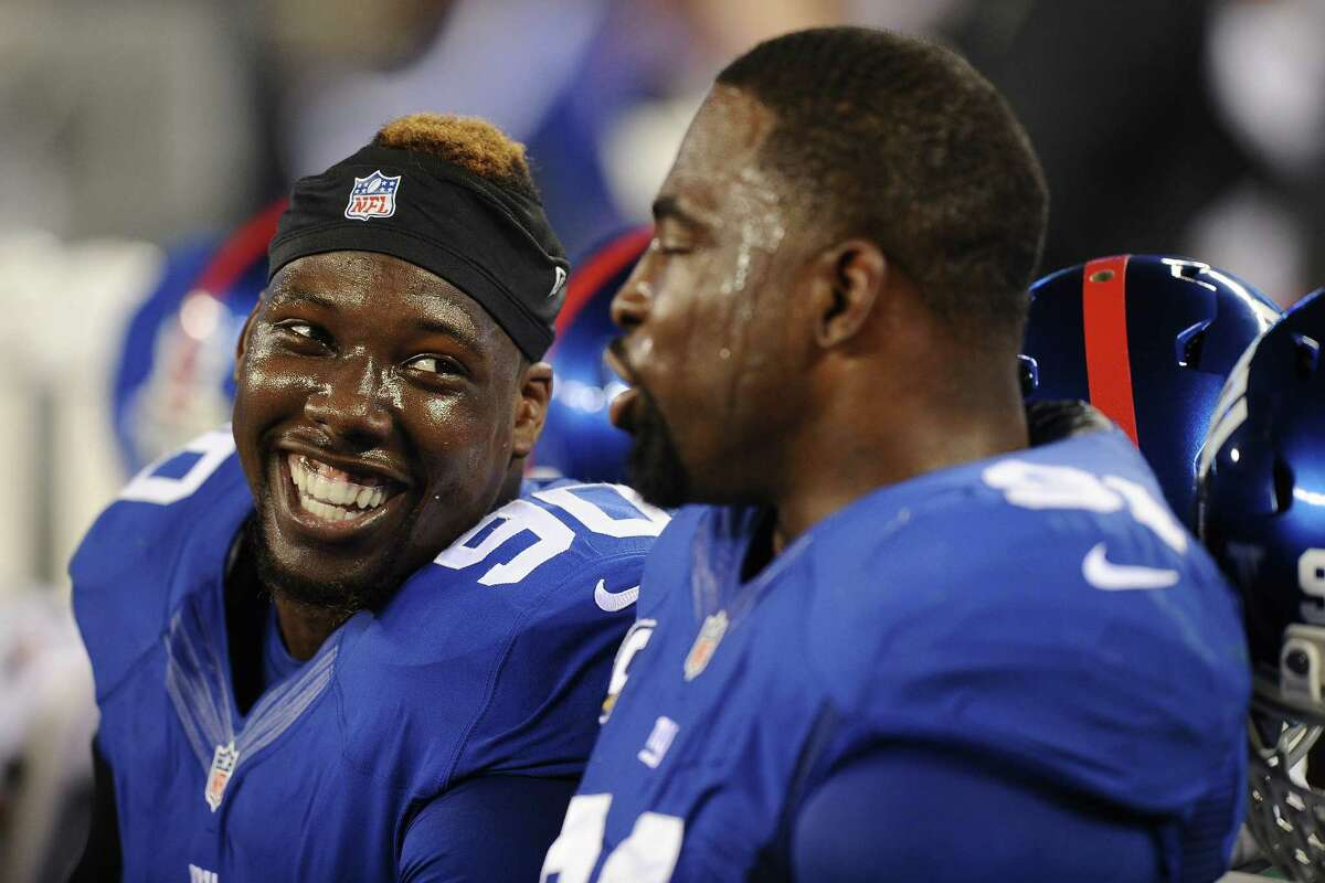 EAST RUTHERFORD, NJ - NOVEMBER 17: Jason Pierre-Paul #90 talks with Justin Tuck #91 of the New York Giants on the bench during the fourth quarter against the Green Bay Packers at MetLife Stadium on November 17, 2013 in East Rutherford, New Jersey. The Giants defeat the Packers 27-13. (Photo by Maddie Meyer/Getty Images) ORG XMIT: 184893009