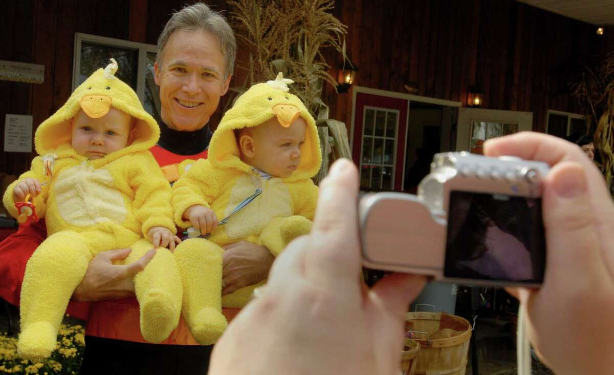 Sunday Oct. 1, 2006, West Sand Lake, NY, In the center Dr. Peter Horvath, a Reproductive Endocrinologist, and a doctor at the fertility medical practice, Albany IVF holding a set of twins he helped their family conceive for a photo by the children's mom. The boys dressed as ducks, are at left, Emmett, and at right Miles, age 8 months, of the Peterson family of Rotterdam, visiting the fourth annual Baby Harvest Festival, held at Hoffay Farms. The harvest, reunites families who conceived through Albany IVF.