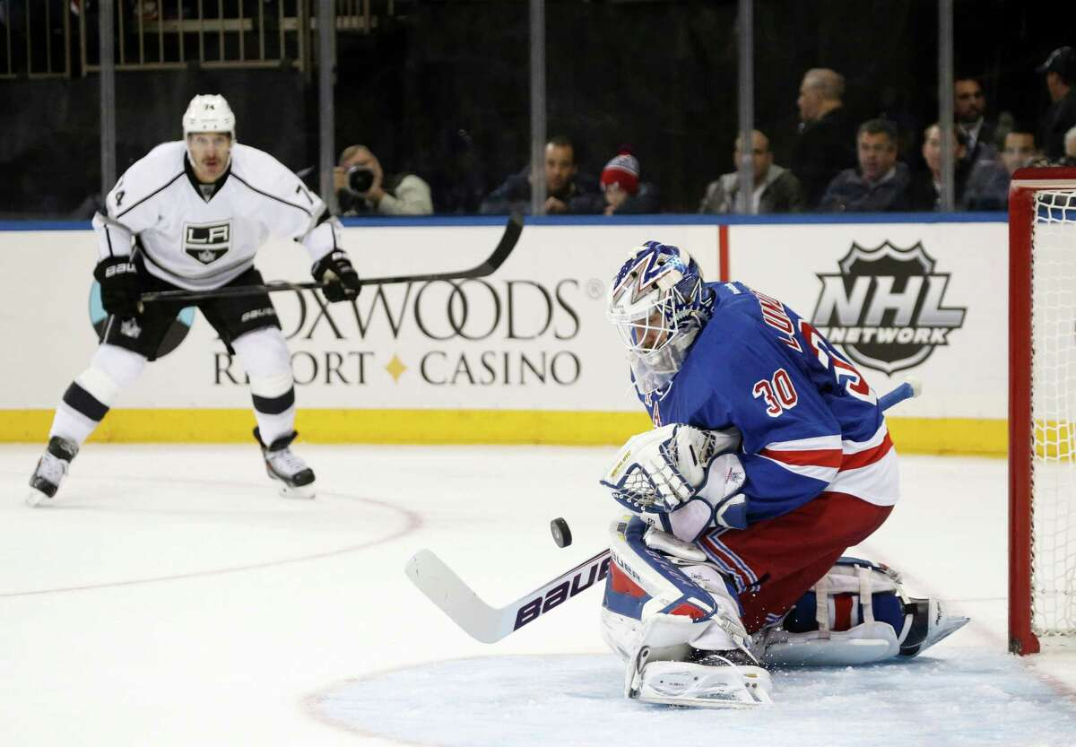 Los Angeles Kings left wing Dwight King (74) watches as New York Rangers goalie Henrik Lundqvist (30) makes a save in the first period of their NHL hockey game at Madison Square Garden in New York, Sunday, Nov. 17, 2013. (AP Photo/Kathy Willens) ORG XMIT: MSG101