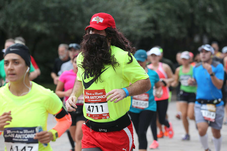 Dressed like Forrest Gump with a nod perhaps to the Boston Red Sox, a participant runs through Alamo Plaza at the Rock 'n' Roll San Antonio Marathon and ½ Marathon. Photo: Photos By Jerry Lara / San Antonio Express-News