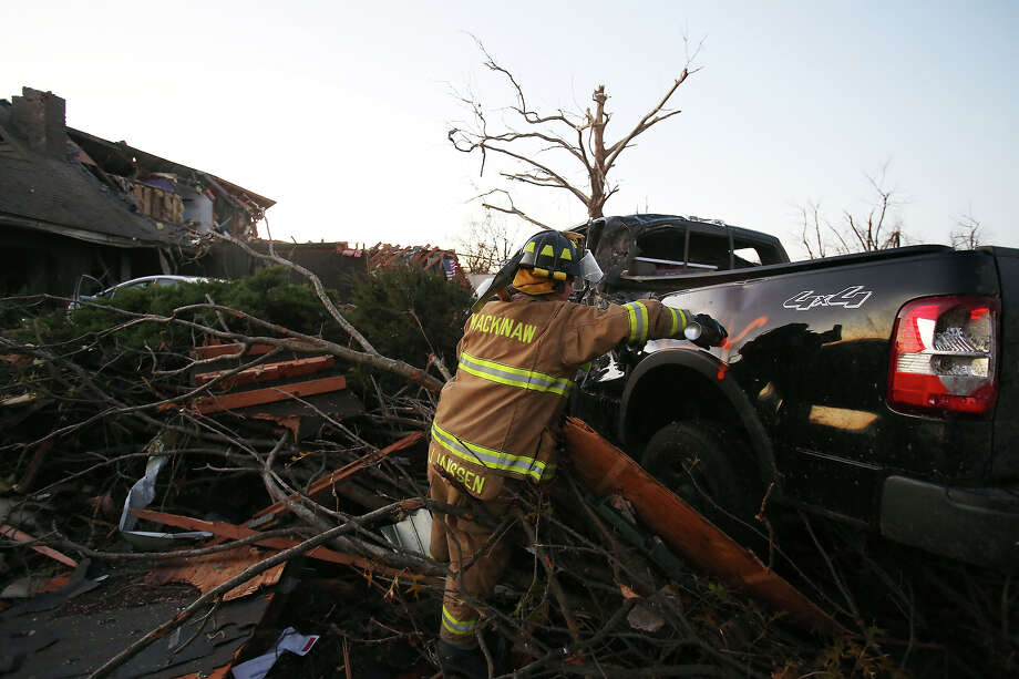 Jeremy Janssen of Mackinaw Fire Department marks a vehicle amongst the debris after a tornado struck on November 17, 2013 in Washington, Illinois. Several tornadoes touched down across the Midwest today with at least three people reported dead in Illinois. Photo: Tasos Katopodis, Getty Images / 2013 Getty Images