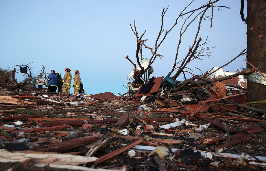 Residents and firefighters sort through debris after a tornado struck on November 17, 2013 in Washington, Illinois. Several tornadoes touched down across the Midwest today with at least three people reported dead in Illinois. Photo: Tasos Katopodis, Getty Images / 2013 Getty Images