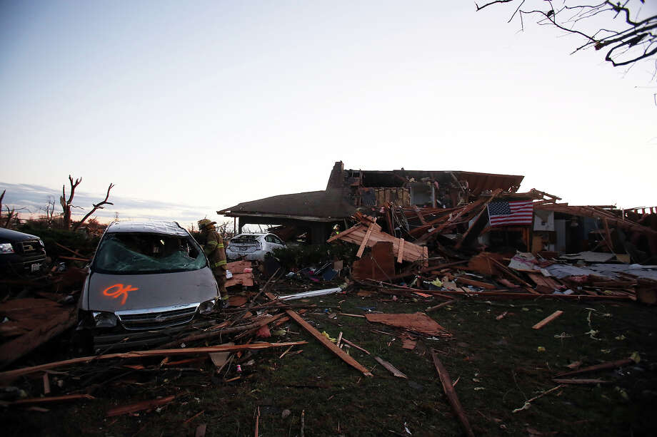 A firefighter searches through debris after a tornado struck on November 17, 2013 in Washington, Illinois. Several tornadoes touched down across the Midwest today with at least three people reported dead in Illinois. Photo: Tasos Katopodis, Getty Images / 2013 Getty Images